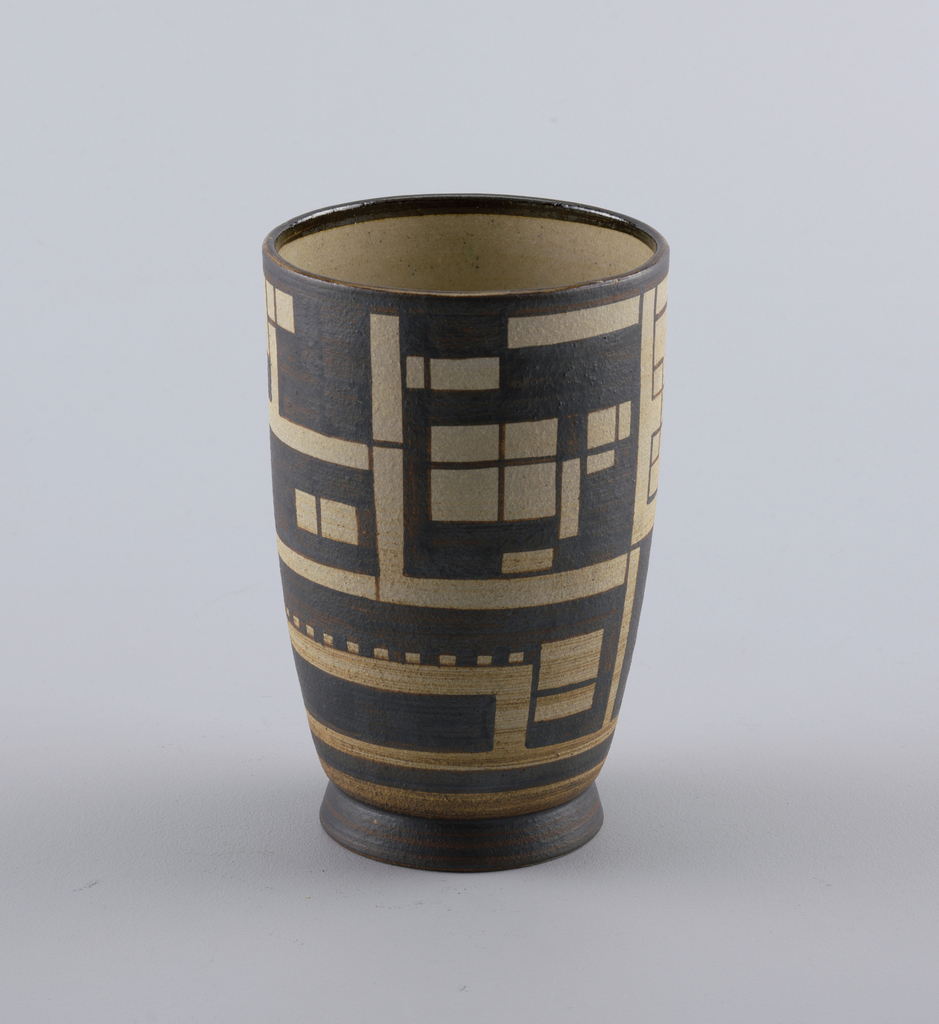Footed vase with slightly straight sides decorated with horizontal and vertical geometric shapes in beige on a black ground.