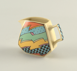 Playful six-sided jagged-shaped creamer in bright colors of orange, yellow, green and blue with bold black outlines of jagged shapes, checkerboard, dots, and lines. Sharply pointed spout and handle with checkerboard pattern.