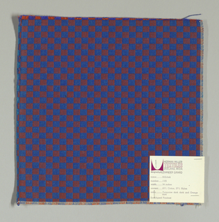 Double cloth in a dark orange and blue checkerboard pattern. The warp threads are blue-violet and orange, and the weft threads are blue and turquoise. The blue-violet warp and turquiose weft intersect and appear as bright blue. The orange warp and blue weft intersect and appear as dark orange.