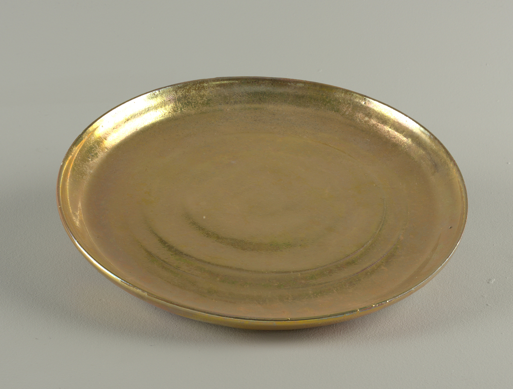 Circular wheel-thrown plate; flat base with upturned rim. Glazed upper surface and on reverse of rim with iridescent polychromatic lustre. Underside within foot ring unglazed.