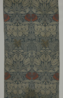 Length of woven wool with a symmetrical repeating pattern of stylized roses and tulips, with foliage forming an ogival framework, with the tulips woven in dark and light blue-green, and the roses in red and ochre.