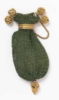 Green silk purse with gilt beads at intersections of mesh. Gilt metal ring to slide and close. Top fitted with bars , with filigree gold pendant.