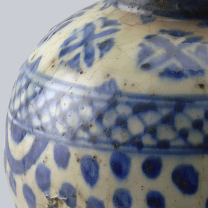 Body swells at upper section, raised rim.  Glazed white background; a wide band of blue dots intersperced with larger blue concentric circlular motifs; above that a diapered band,  at top a band of crossed circular motifs; blue band at rim.