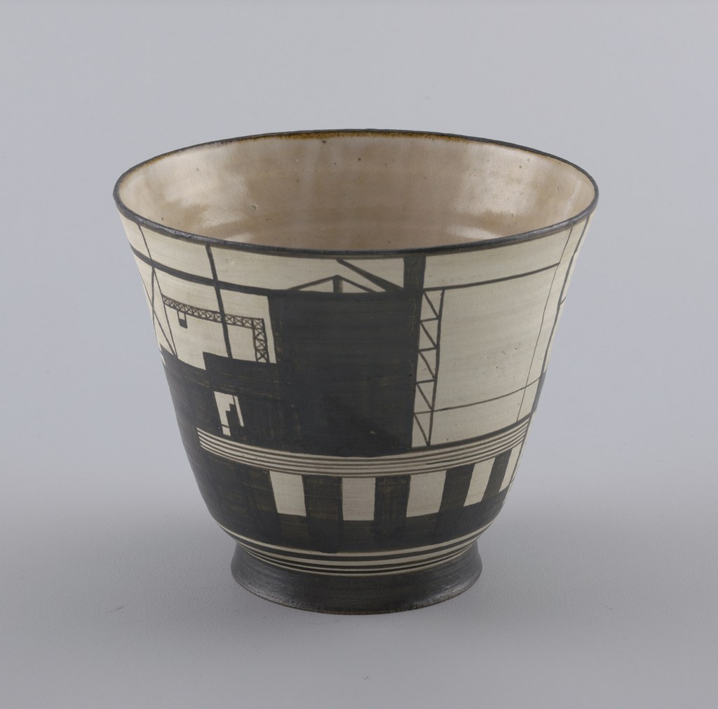 Thrown circular vase, collared foot ring; sides flared toward lip.  Interior glazed translucent cream color.  Exterior with white slip ground, painted black squares, lines and rectangles to suggest a urban landscape, all highly stylized and schematic.  Exterior unglazed.