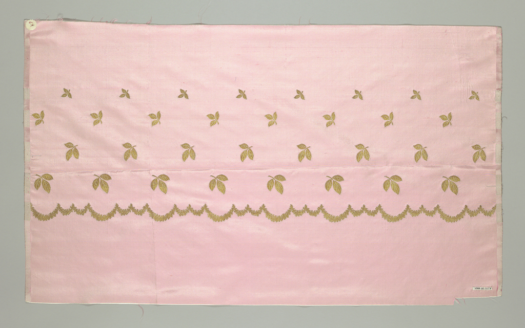 Taffeta fabric with a border design of a scalloped line and leaves in metallic gold thread. There are four rows of leaves that are graduated in size with the largest leaves closet to the scalloped line.
