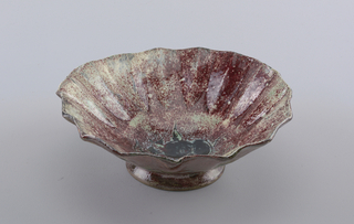 "Bowl rests on circular foot. Sides irregularly pleated, with pleats flaring up and out at extreme angle to creat concavity. Exterior glazed in mottled red and green with calligraphic brushstrokes in black around foot. Interior glazed in heavily mottled red and pale green; in center of interior a branch with leaves and fruit incised and painted in black. Artist's monogram and ""68"" incised in center to side of fruits."