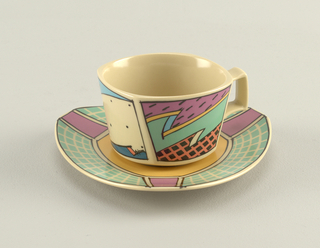 Square-shaped cup with slightly rounded corners decorated in bright colors of pink, orange, yellow, green and blue with bold black outlines of jagged shapes, checkerboard, dots, and lines. Square handle painted with blue and black checkerboard pattern. Saucer triangular with rounded sides; decorated in yellow at well, grid pattern on rim in light green and white, with pink rectangular panels at corners.