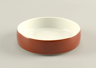 Circular form with upright convex rim; white body with cinnamon-brown glaze on exterior.