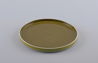 Flat circular form with slightly concave upright rim; white body glazed olive green on interior, green on exterior rim.