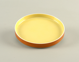 Flat circular form with slightly concave upright rim; white body glazed yellow on interior, orange on exterior rim.