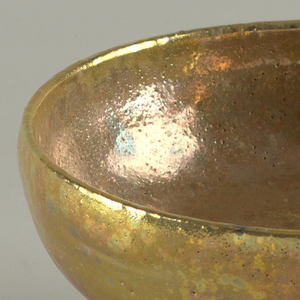 Circular deep bowl with curved sides on cylindrical flared foot. Glazed with iridescent polychromatic lustre. Inside of foot unglazed.