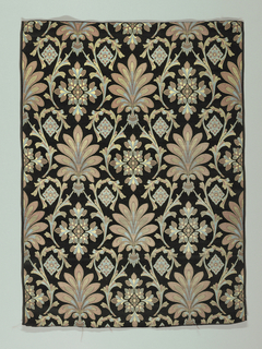 Woven silk with a highly stylized design of palmettes and floral crosses with curving vines in blue, red and gold on a black ground. Red has faded into rust on the front.