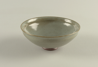 rounded bowl on small foot: slightly everted rim. Dark brown clay with finely crackled grayish celadon glaze with fine speckles.