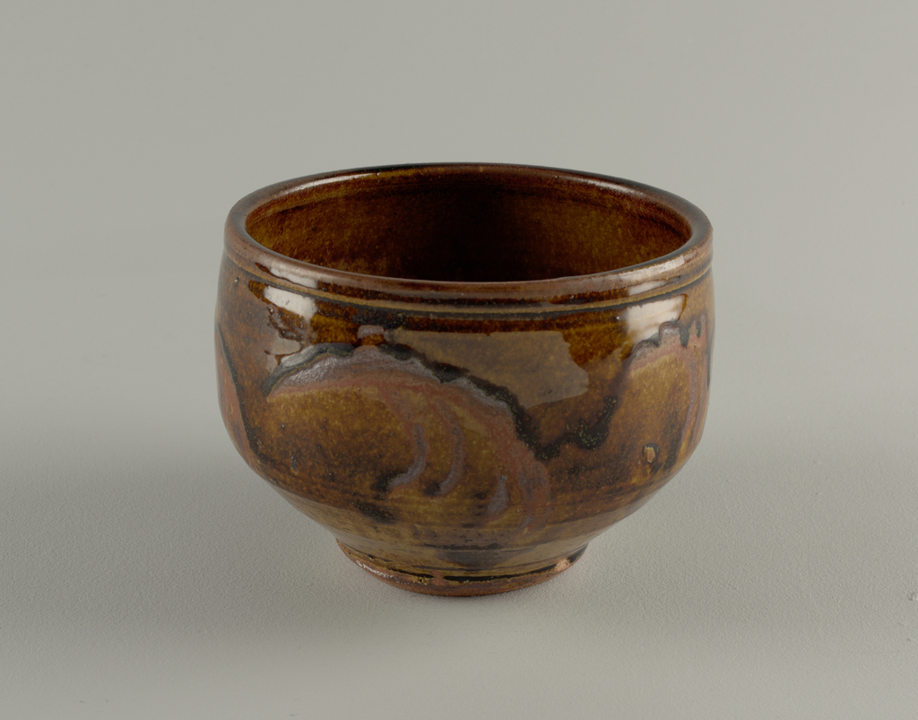 Straight sided, tapering shparlply to base, irregular glaze around sides (browns), mottled brown / yellow glaze interior.