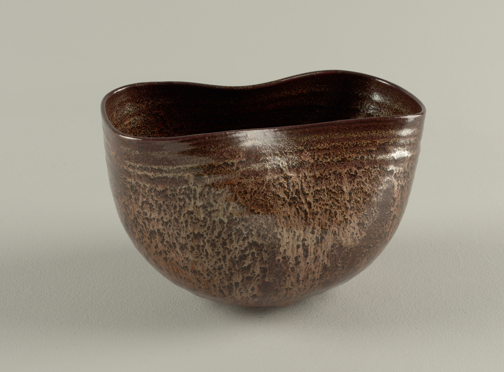"""Rounded bowl, with throwing ridges, squashed to oblong shape in upper part. Aventurine glaze of metallic lustre over red clay. Incised """"A.de C."""""""