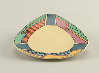 Plate is triangular with rounded sides; well is cream with borders decorated black and blue checkerboard, orange and black stripes, light green, yellow, pink, and panels of purple at corners.