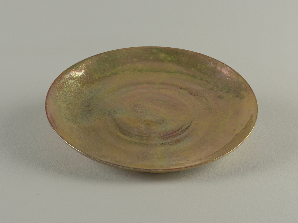 Circular wheel-thrown plate; flat base with upturned rim. Glazed upper surface and on reverse of rim with iridescent polychromatic lustre. Under-side within foot ring unglazed.