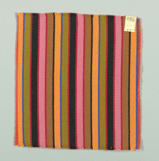 Warp-faced twill weave in broad and narrow vertical stripes of blue, light orange, black, light brown, dark pink, pink and olive green. Binding weft threads in dark pink on the reverse.