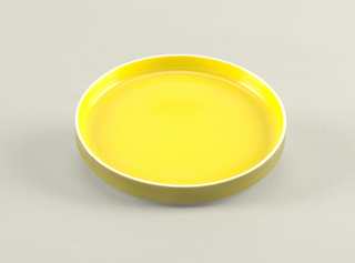 Flat circular form with slightly concave upright rim; white body glazed yellow on interior, green on exterior rim.