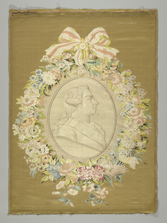 A woven portrait of the Comte de Provence is embroidered to the fabric that forms the frame. The frame is a woven wreath of multicolor flowers with a bow at the top.
