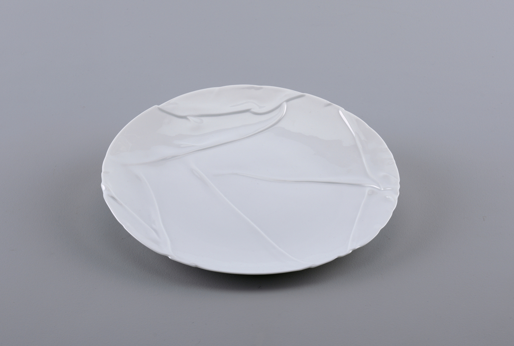 White porcelain plate with molded decoration that appears as though folded.