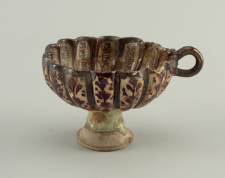 On tall, hallow foot a bowl with fourteen flutings and small handle. Greenish white glaze, with brown outlining the scallops and in staggered leaf motifs on outside and geometric line decoration on inside.