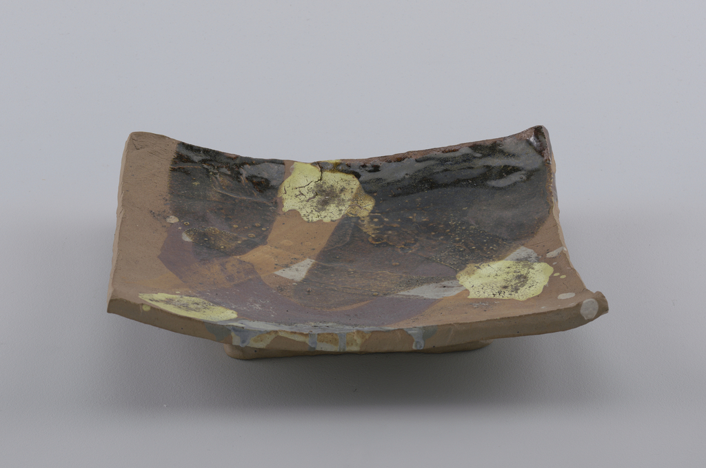 Square slab, slightly dished, on fott. Brownish, coarse clay, streaked and splashed with vari-colored glazes and pigments.