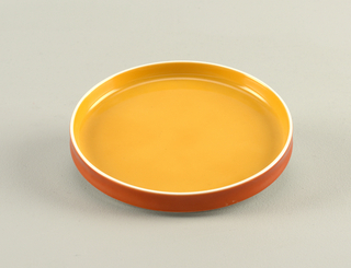 Flat circular form with slightly concave upright rim; white body glazed yellow-orange on interior, orange on exterior rim.