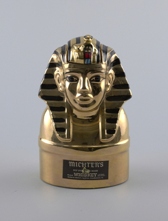 Whisky bottle, Ceramic, in the form of the fifth death mask of King Tutankhaman washed with 23 carat gold, and associated packing and advertising material.
