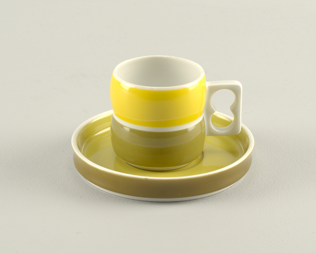 Cup (a): cylindrical white body formed of two convex sections, one above the other, white pierced rectangular handle on side; exterior of top section glazed in yellow, bottom section in light green. Saucer (b): circular form with slightly concave upright rim; white body glazed light green on interior, green on exterior rim.