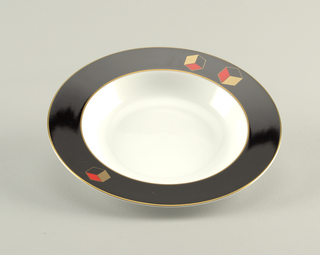 Deep dish with bright white well; border in solid black with gilt rim, and three three-dimensional cubes in gold, red, and black; two on one side and one on the other.
