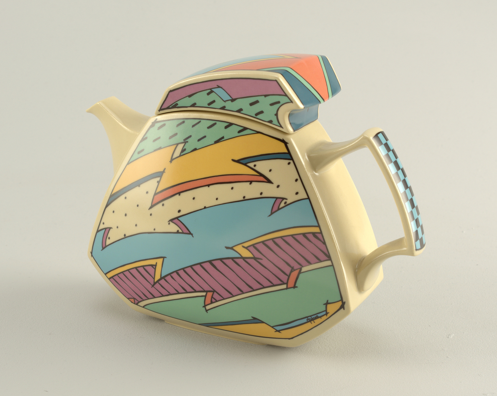 Playful six-sided jagged-shaped teapot and lid in bright colors of pink, yellow, green and blue in bold black outlines of jagged shapes, checkerboard, dots, and lines. Angular spout and handle with checkerboard pattern.