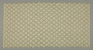 Light tan textile patterned by slits caused by the discontinuous wefts. Pattern based on a diamond.