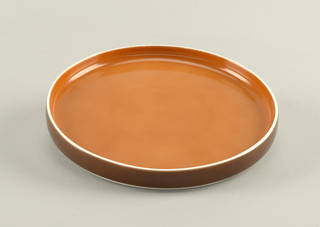 Flat circular form with slightly convex upright rim; white body glazed orange on interior, brown on exterior rim.