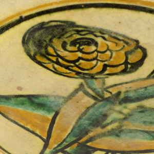 """Circular plate decorated with stylized image of a large flower and bud with broad leaves, in palette of yellow, green, black on white ground; white rim with black and yellow bands. """"HVP"""" to lower right of flower stems."""
