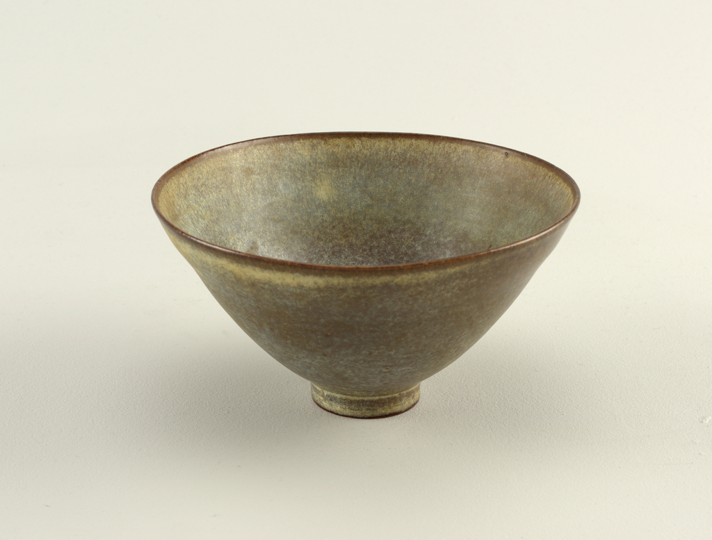 Footed flared bowl; interior incised decoration in fish motif.