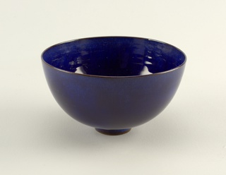 "Circular bowl with curved sides, plain lip, and small circular foot. Glazed in oxidation-fired ""mystic"" blue. Underside of foot ring unglazed. Glaze thin around foot ring and in center of bowl."