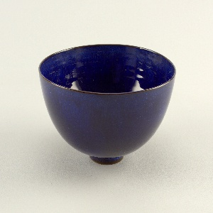 """Circular bowl with curved sides, plain lip, and small circular foot. Glazed in oxidation-fired """"mystic"""" blue. Underside of foot ring unglazed. Glaze thin around foot ring and in center of bowl."""