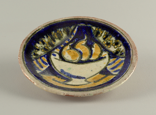 Circular plate decorated with stylized still life of pears in a footed white bowl before flowered curtains, glazed in a palette of yellow, blues, and white, within a mottled blue border; narrow rim glazed in mottled white.