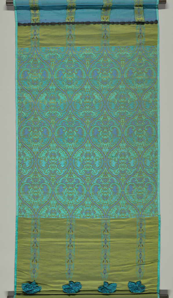 Window shade in tones of blue, turquoise and yellow-green has ogival forms filled with a scrolling vine pattern. Top and bottom sections have horizontal bands of yellow-green with narrow vertical stripes. Vertical stripes finished with tassels at the bottom edge.