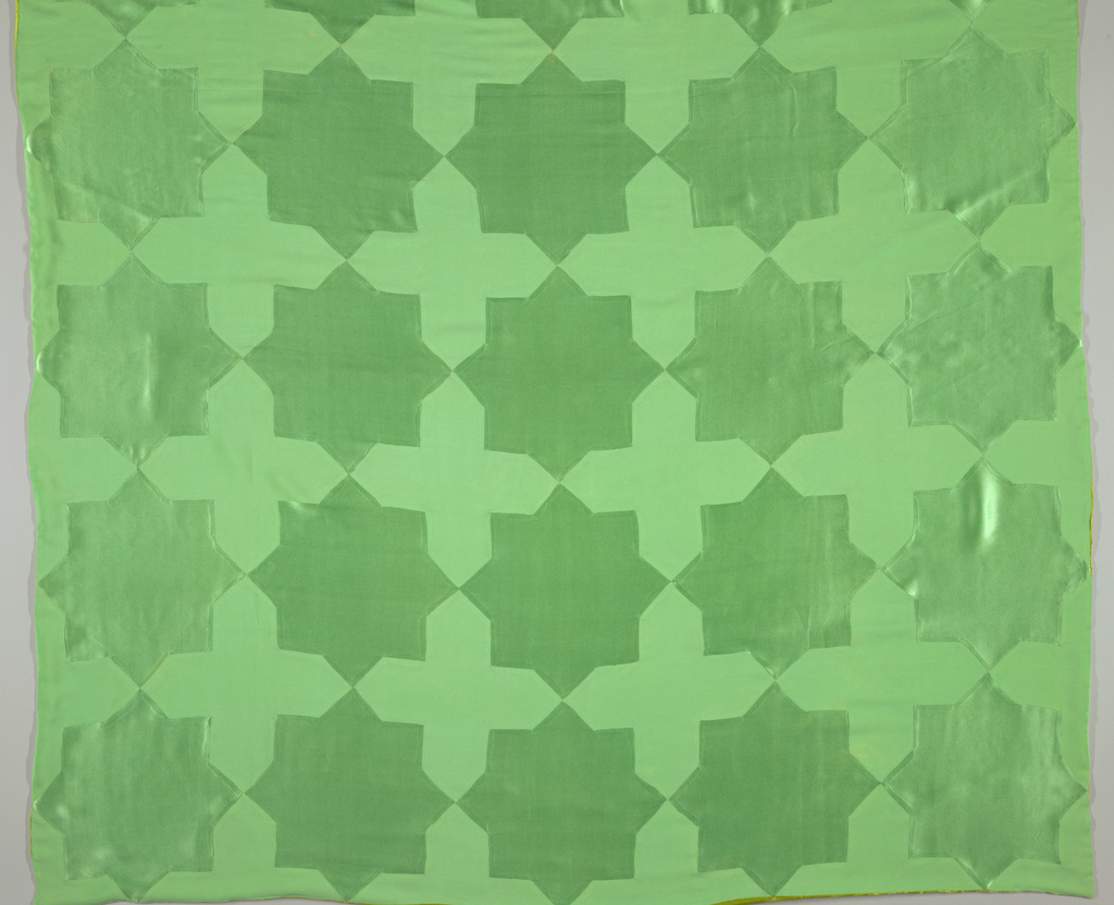 Large square, made up of pale jade green forms, an eight-pointed star, a Greek cross with pointed arms, fitted and sewn together. Stars are in shiny satin, crosses are in creped silk satin with dull finish. Lined with chartreuse crepe into whose borders are inserted half-crosses in shiny chartreuse satin.