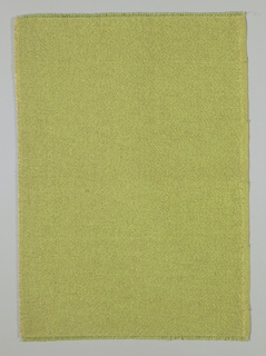 Firmly woven yellow-green textile with warps of novelty yarn. Wefts of mohair are wound loosely with narrow gold strips. One plain cloth selvage with cotton warps.