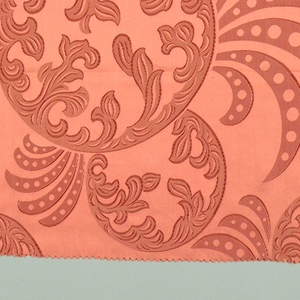 Coral-colored satin with large-scale horizontal repeat of circular foliate medallion with pointed leaves or feathers radiating out from the edge.