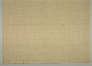 Tablemat made of Irish linen dyed with iron rust in a pattern of closely set openwork squares.