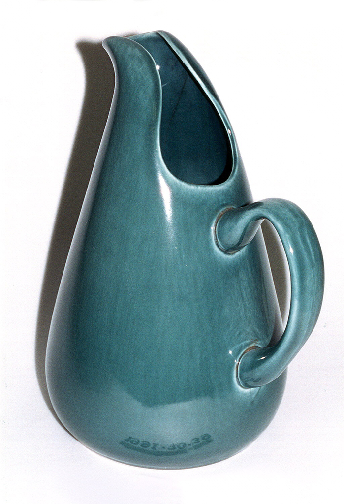 """Tall tear-shaped pitcher with tapered mouth rising to spout; angled D-form handle; """"seafoam green"""" glaze."""
