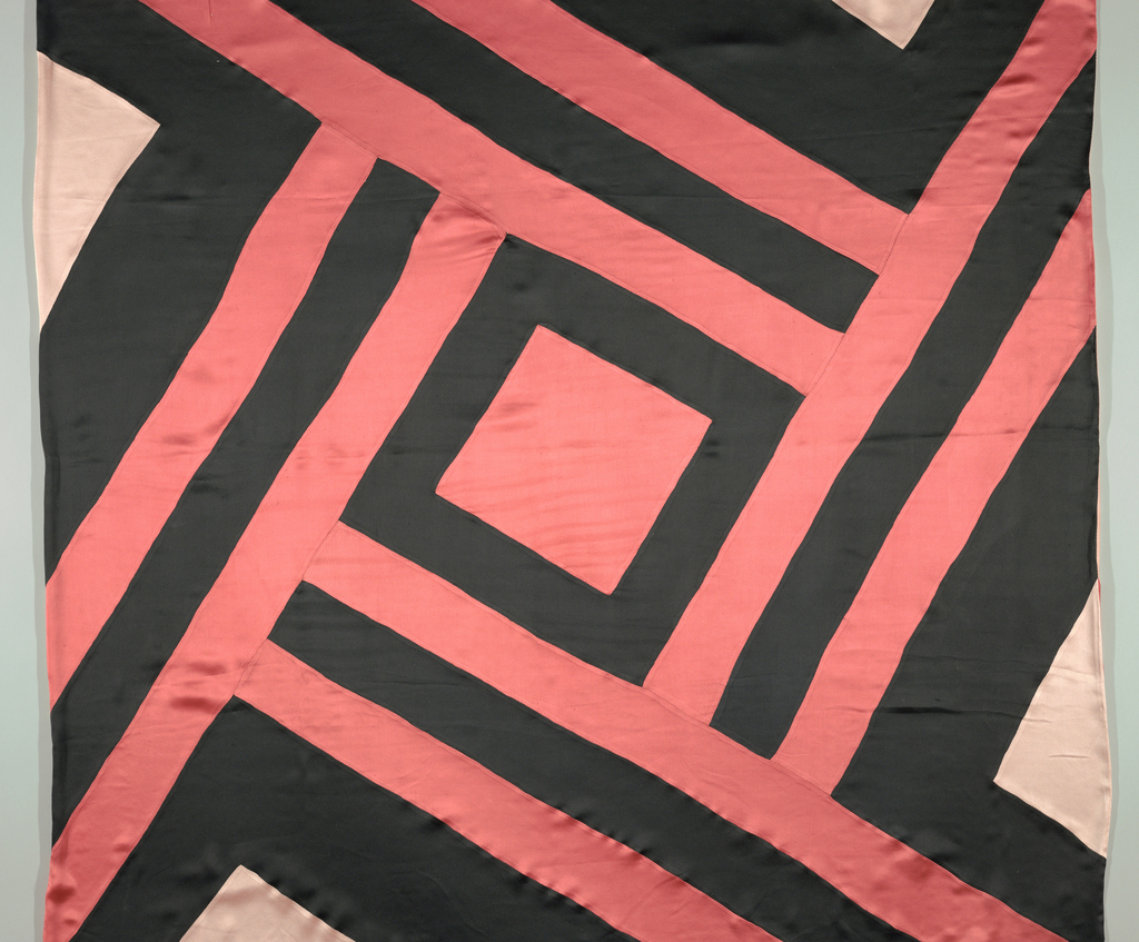 Square scarf composed of strips of black and coral satin sewn together to form central square with large simple lattice around it. Lined with pale pink satin, some of which appears on edges of face in triangles, and triangles of coral appear on reverse.