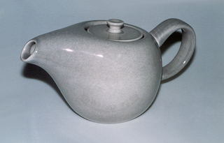 Gray teapot with applied loop handle and mouth-like spout, flush lid with button finial.