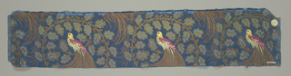 Sample with a blue satin ground and a staggered horizontal repeat of scrolling branches in gold with brown berries. Bird with body brocaded in yellow, green, and cerise silks and a long brown tail perches on the tip of a branch.