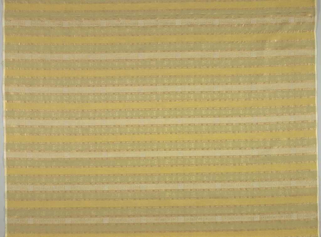 Panel woven with small-scale pattern in imitation of an Islamic silk with inscription. Pale shades of green and yellow with white inscriptions interspersed with horizontal bands of gold Lurex.