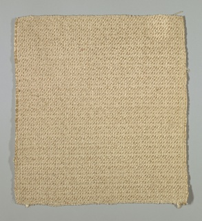 Coarsely textured textile in light brown woven with Z-twist and slubbed novelty yarns that are matte and shiny.